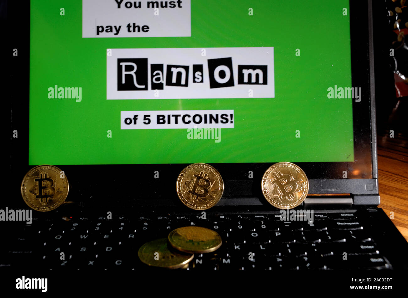 """Five """"bitcoins"""" on a laptop displaying a ransom message demanding 5 bitcoins. Stock Photo"""