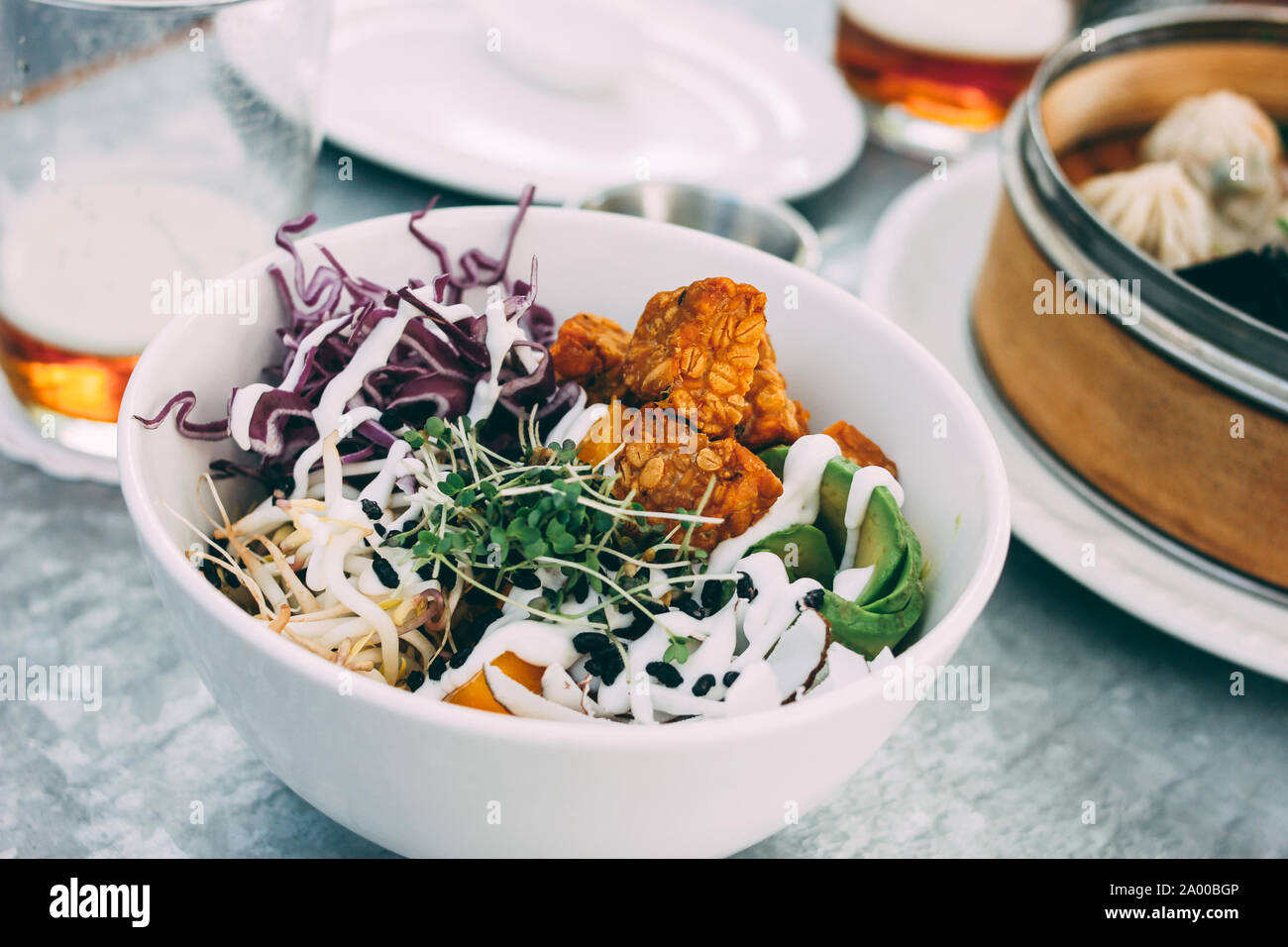 Pan-Asian food - the vegetable salad bowl and different dim sums. Lunch for two with beer Stock Photo
