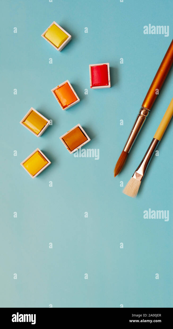 Paint brush and warm color palettes of red, orange and yellow, with blue background. Stock Photo