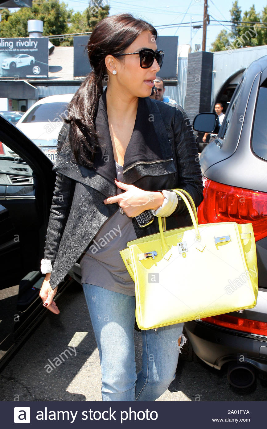 Beverly Hills, CA - Kim Kardashian took her white Rolls Royce to Platinum Motor Sports this afternoon and dropped it off to get some new customization done. As Kim left, a couple lucky fans spotted her and flagged her down to take a picture with her. GSI Media June 21, 2011 Stock Photo