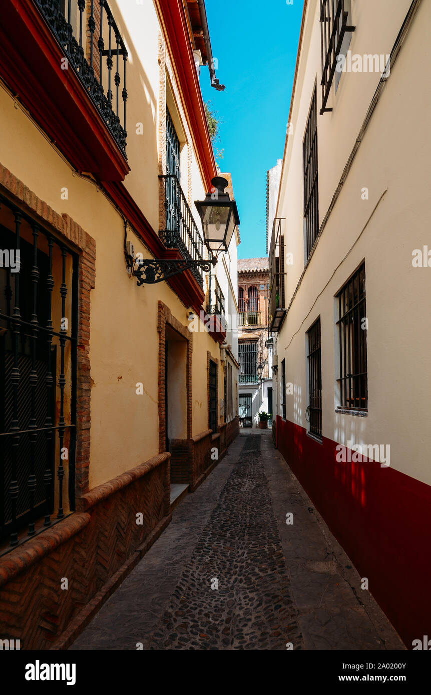 Old picturesque passageway in the medieval Jewish Quarter of Santa Cruz in Seville, Andalusia, Spain. Stock Photo