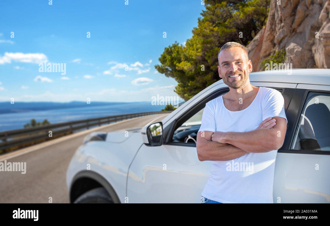A young man stands near a car on a background of the sea coast. Stock Photo