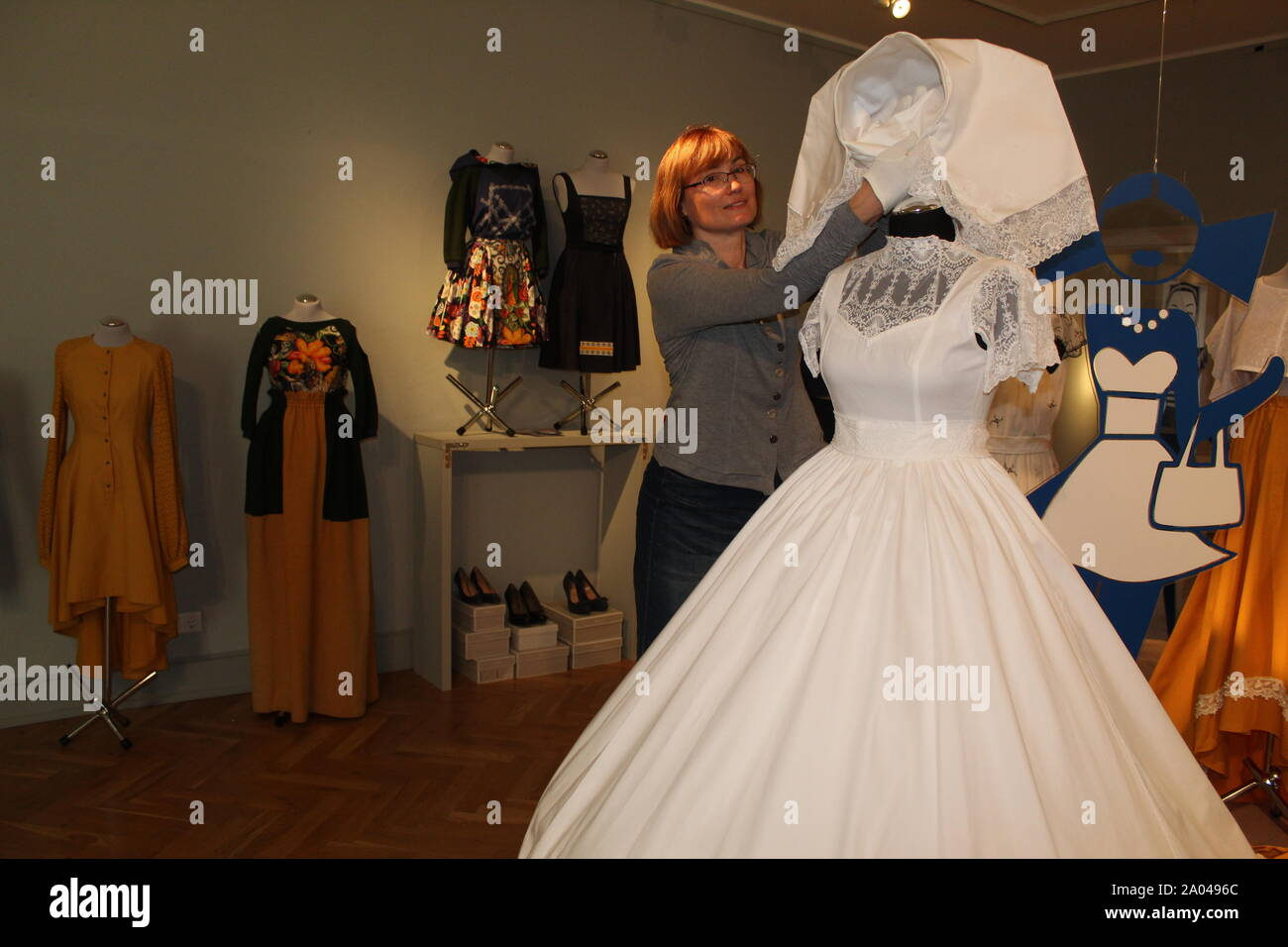 """19 September 2019, Saxony, Bautzen: The exhibition curator Andrea Paulick in Sorbian Street Style stands in the exhibition """"Sorbian Street Style"""" in the Sorbian Museum next to a modern Sorbian wedding dress. The traditional costumes disappear more and more from the everyday life of Lusatia. The Sorbian Museum Bautzen is now showing how traditional patterns, colours, cuts and shapes can be turned into wearable everyday fashion. (to """"Exhibition """"Sorbian Street Style"""": Creative inspirations from the chest"""") Photo: Miriam Schönbach/dpa-Zentralbild/ZB Stock Photo"""