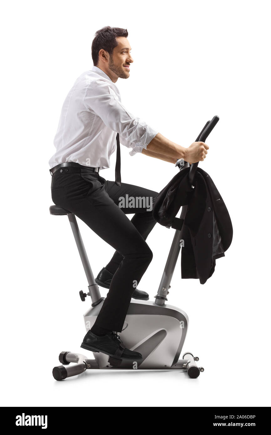 Full length profile shot of a young man in formal clothes exercising on a stationary bike isolated on white background Stock Photo