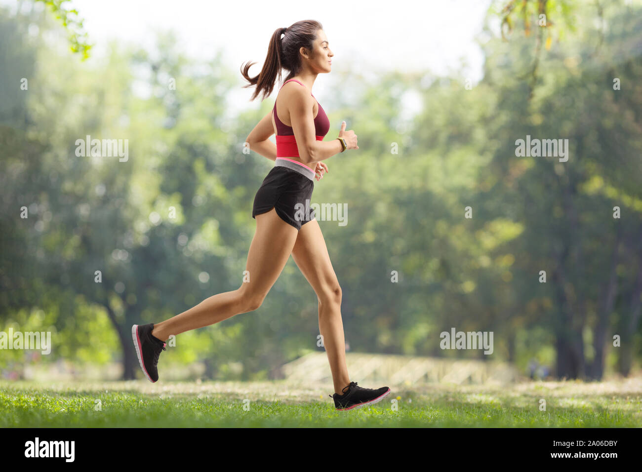 Full length profile shot of a young female athlete jogging outdoors Stock Photo