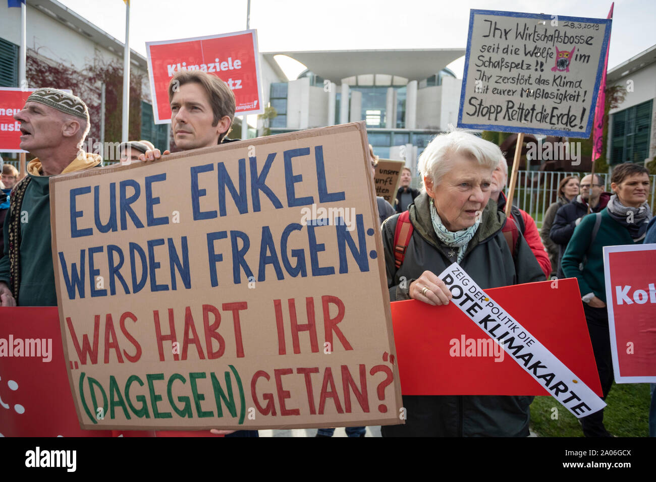"""Berlin, Germany. 19th Sep, 2019. A participant of a climate protest of the non-governmental organisation Campact holds a banner in front of the Federal Chancellery with the inscription """"Your grandchildren will ask: What have you done (against it)? Credit: Christoph Soeder/dpa/Alamy Live News Stock Photo"""