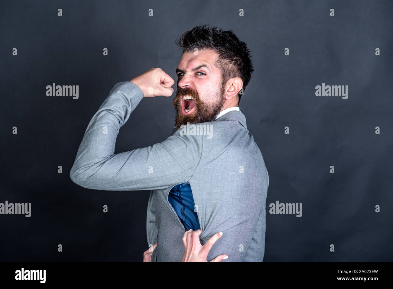 Angry guy bought counterfeit or fake brand. Man with beard wears jacket with hole on dark background. Hipster chose small size jacket, seam torn with Stock Photo