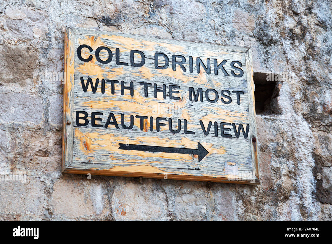 """Well known sign """"Cold drinks with the most beautiful view"""" giving directions to the Buza bar for sunset drinks; Dubrovnik old town, Croatia Europe Stock Photo"""