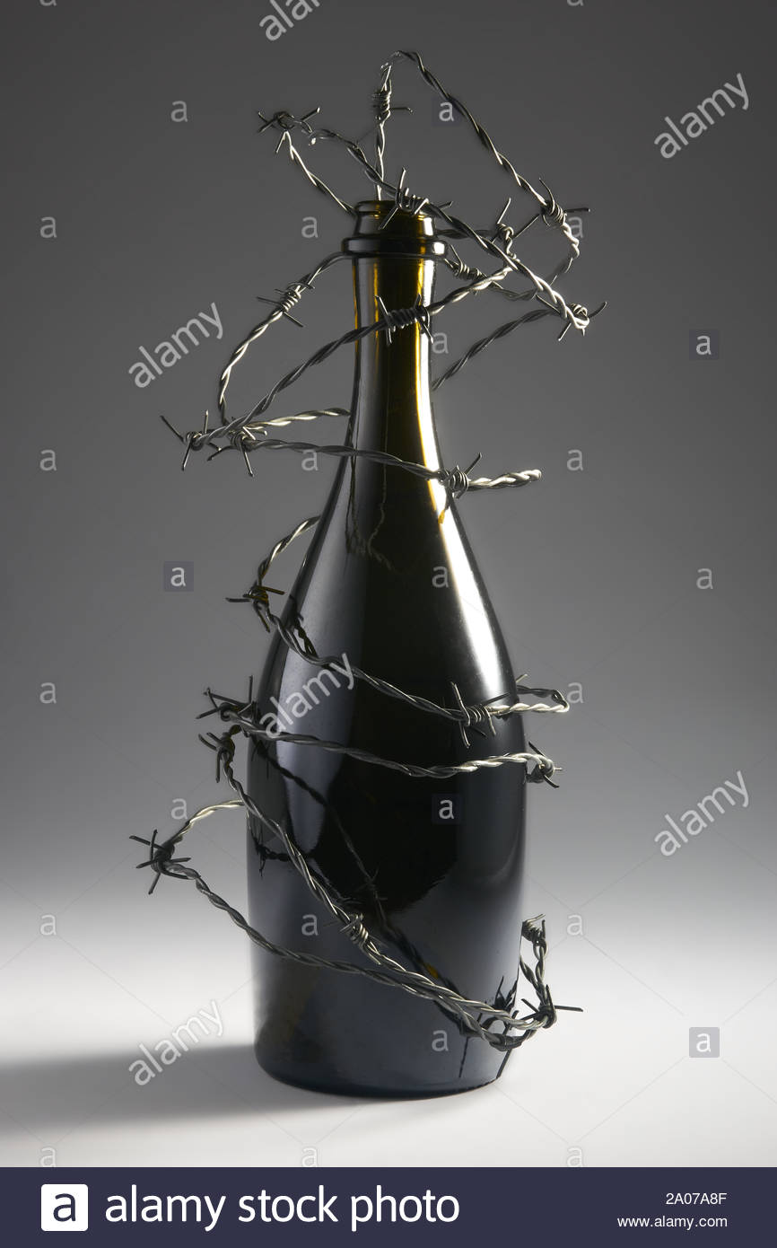Barbed wire blocks alcohol bottle. Isolated on dark background. With copy space text. Studio Shot. Stock Photo