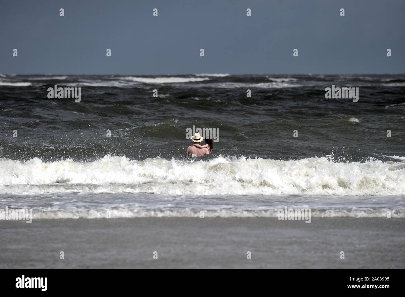 A man with a hat and a child in his arms is walking towards the waves (North Sea, Langeoog, Germany). Stock Photo