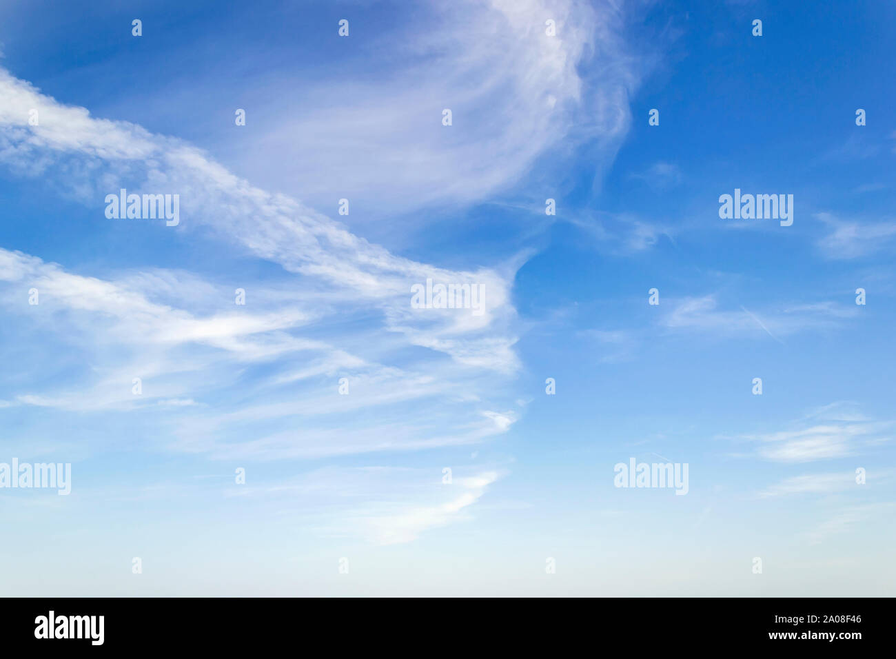 Scenic skyscape with fluffy cirrus and stratus clouds in the stratosphere. Light spindrift clouds high in the blue sky. Different cloud types. Stock Photo