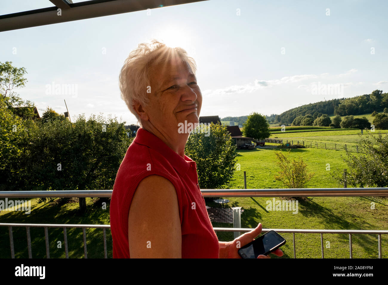 Senior woman with white hair is standing on the balcony looking at her mobile phone. Stock Photo