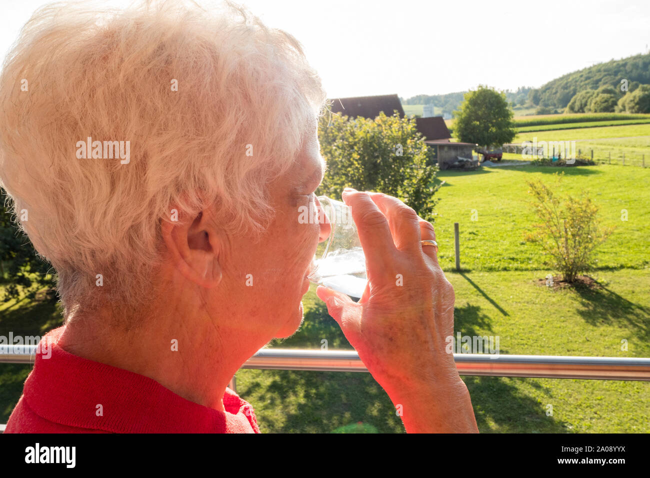 Senior citizen drinking a glass of water in the sun in the garden Stock Photo