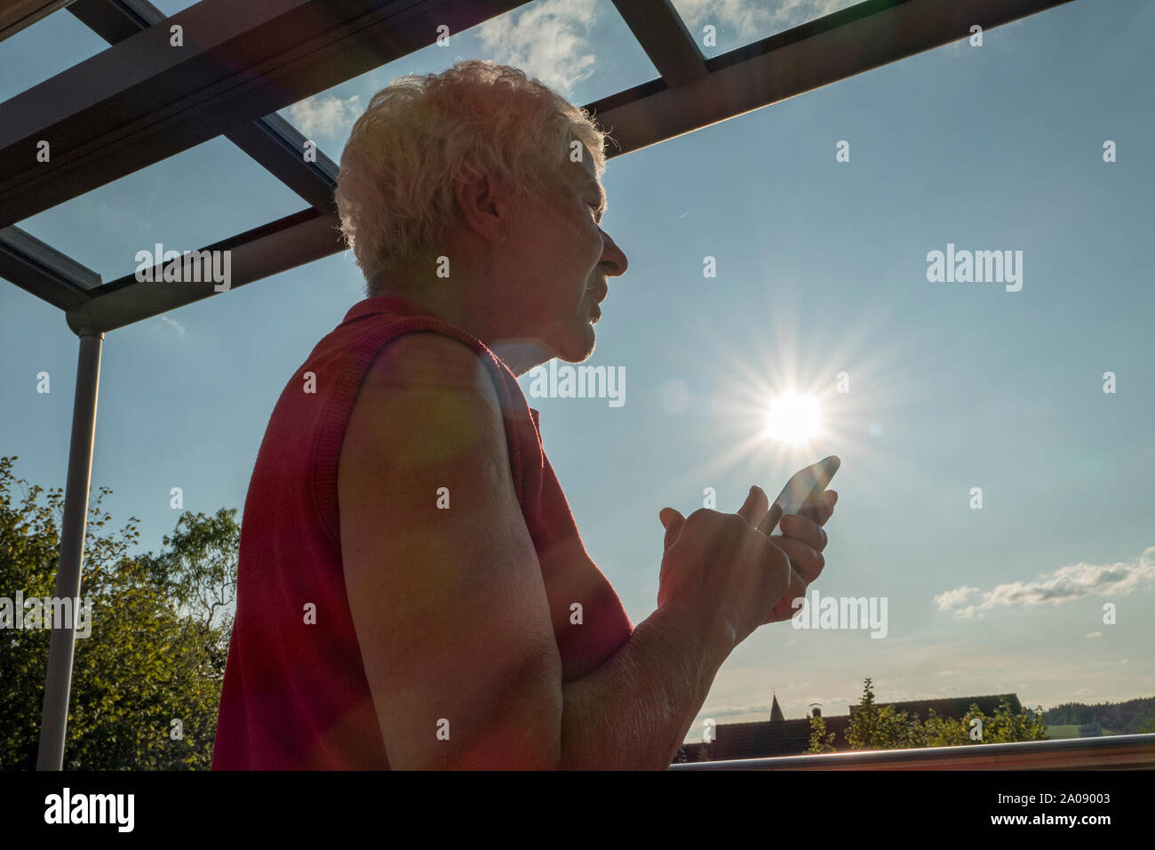 Senior woman trying to read a message in the sun on a cell phone Stock Photo