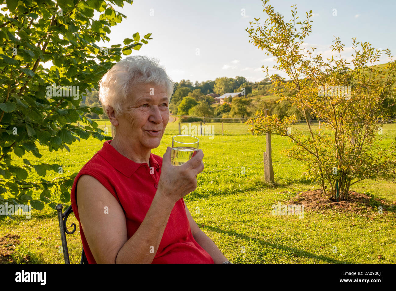old lady sitting comfortably in the garden and drinking a glass of water Stock Photo