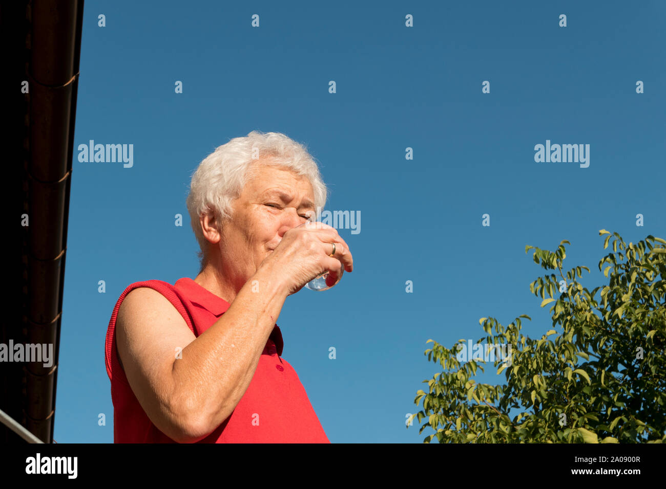 old lady drinking a glass of water in front of a blue sky Stock Photo