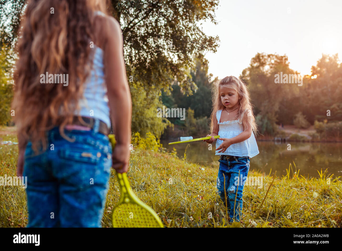 Badminton. Little girl playing badminton with sister in summer park. Kids having fun outdoors. Outdoor games for children Stock Photo