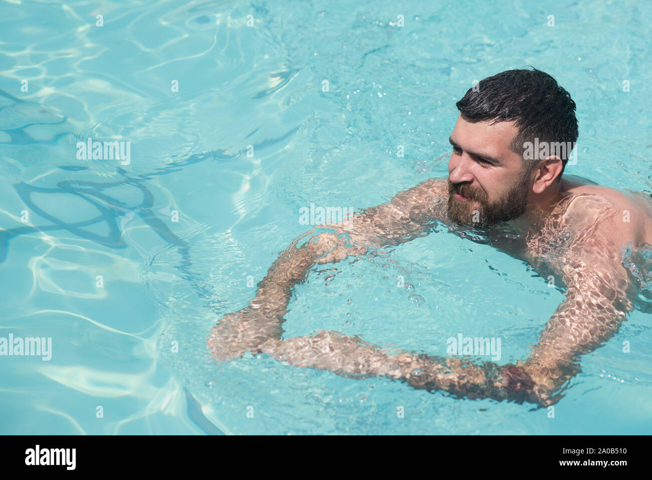 bearded man swimming in blue water. Summer vacation and travel to ocean. Relax in spa swimming pool, refreshment and skincare. Maldives or Miami beach Stock Photo