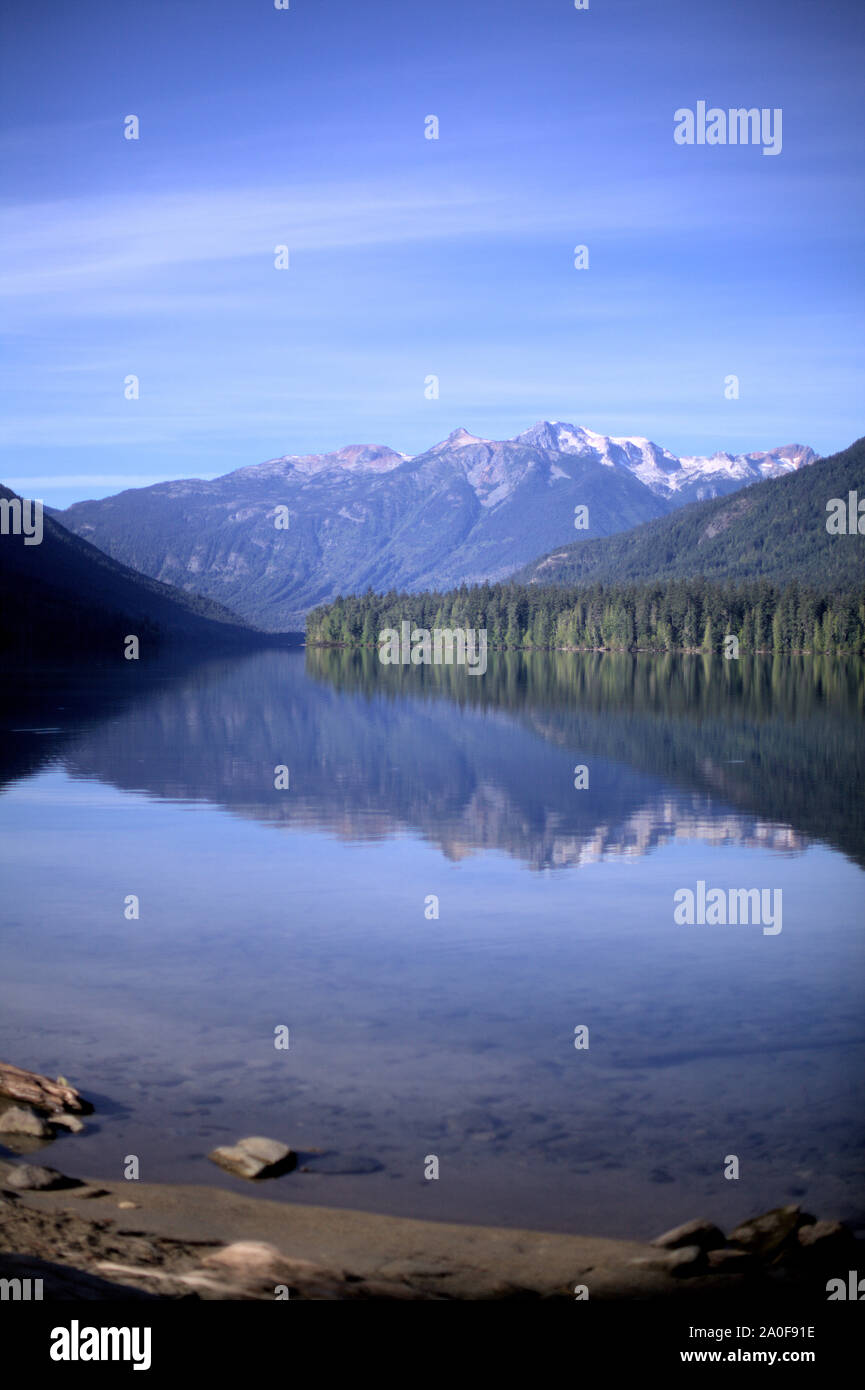 Snow capped mountains, green conifers and blue sky reflecting in Birkenhead lake as in a mirror, on the still water, in a secluded destination of BC Stock Photo