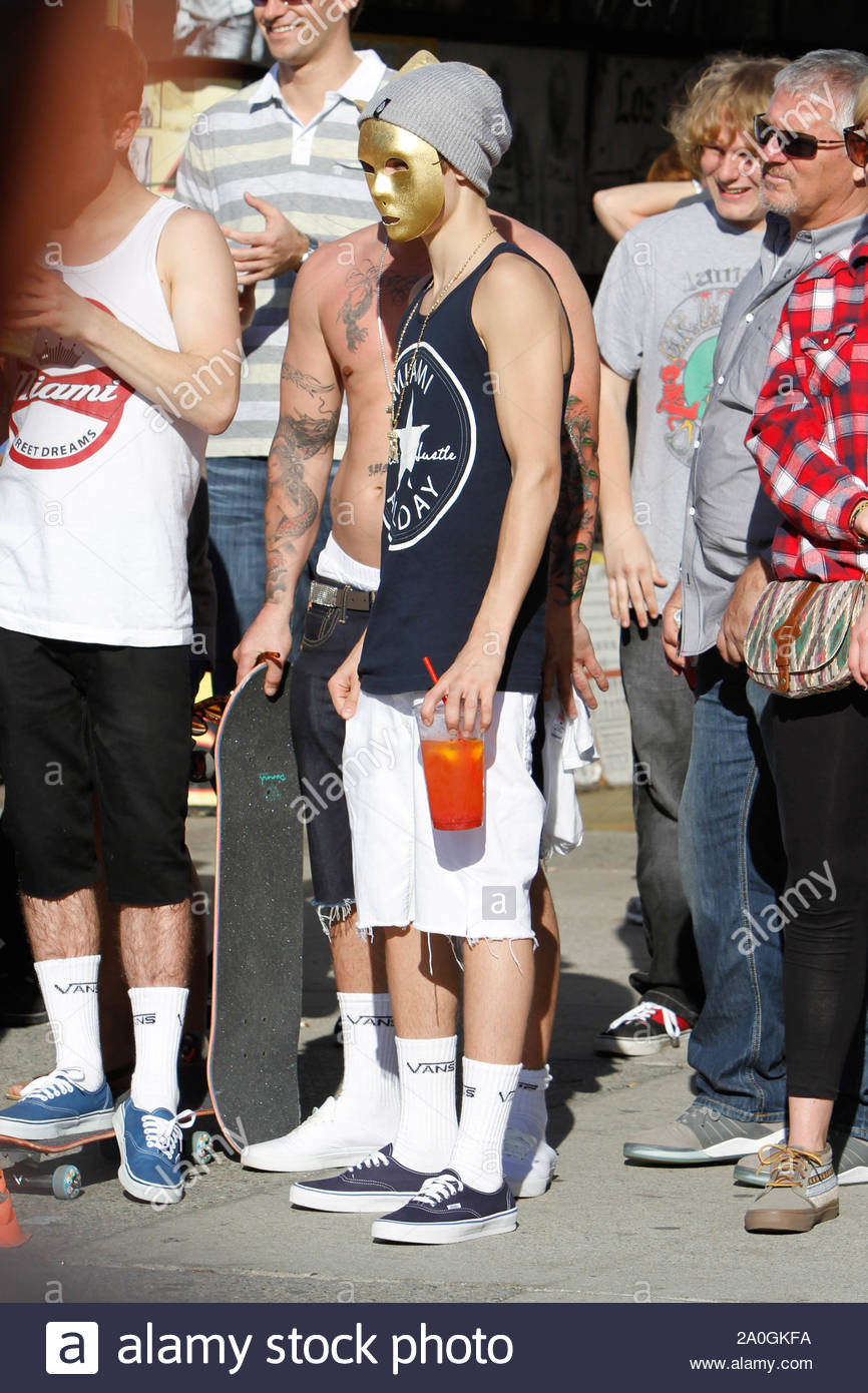 Venice Beach, CA - Justin Bieber went to Venice Beach this afternoon, looking for a day away from his normal schedule. To accomplish that, he decided to wear a gold mask over his face, blocking the world from recognizing him. Along with his dad and best friend, the three played a few hoops and walked up and down the boardwalk, watching the sidewalk performers do what they do best. They also decided to stop at one of the dozens of tattoo shops for some fresh ink. Justin got a tattoo of Jesus Christ on the back of his left calve muscle, while his father chose a tropical flower design running up Stock Photo