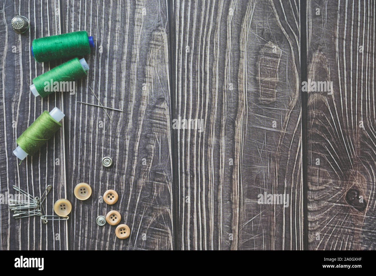 Sewing accessories on dark wooden background. Green sewing threads, needle, buttons and pins. top view, flatlay Stock Photo