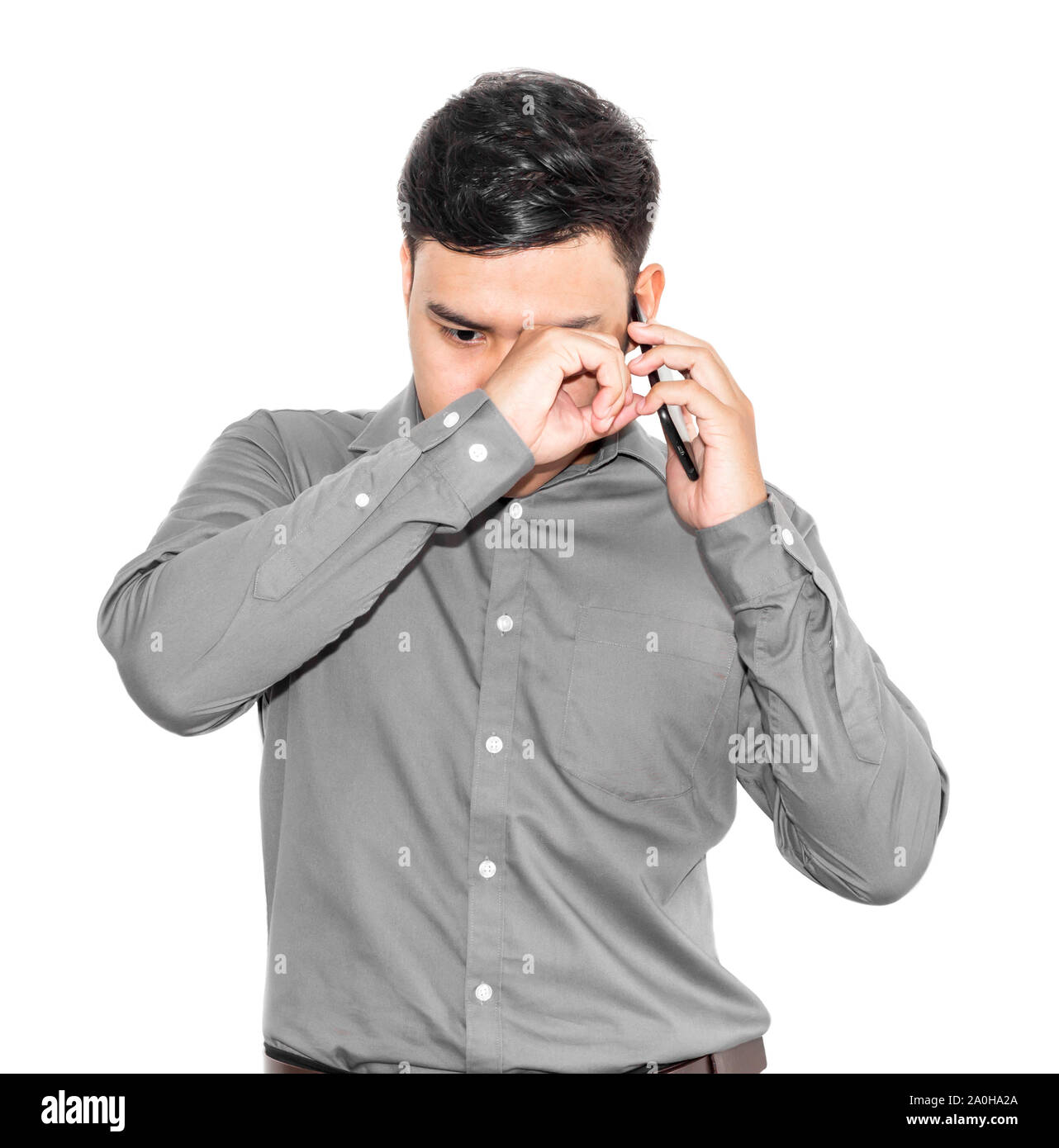 Thai man in a gray shirt is talking on the phone and is sad. Stock Photo