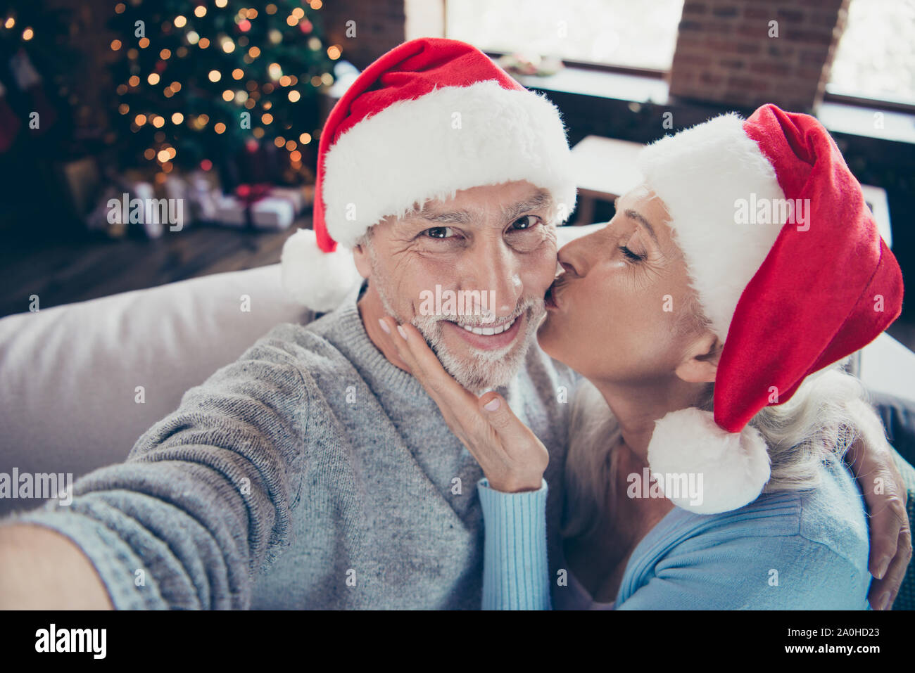 Shoot happiness. Self-portrait of two cheerful glad delighted sweet tender grey-haired married spouses in house cuddling granny kissing his cheek enjo Stock Photo
