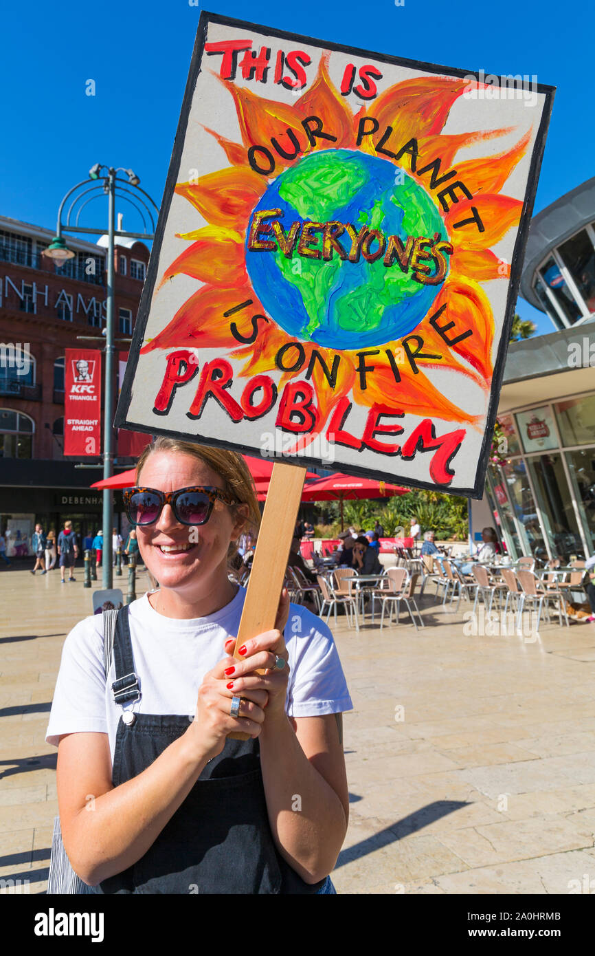 Bournemouth, Dorset UK. 20th September 2019. Protesters, young and old, gather in Bournemouth Square on a hot sunny day to protest against climate change and demand action against climate breakdown from government and businesses to do more. BCP (Bournemouth, Christchurch, Poole) Council have reportedly been threatened with legal action and could be taken to court until they produce proper timely climate change plans. Woman holding placard - our planet is on fire this is everyone's problem. Credit: Carolyn Jenkins/Alamy Live News Stock Photo