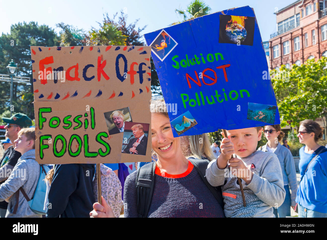 Bournemouth, Dorset UK. 20th September 2019. Protesters, young and old, gather in Bournemouth Square on a hot sunny day to protest against climate change and demand action against climate breakdown from government and businesses to do more. BCP (Bournemouth, Christchurch, Poole) Council have reportedly been threatened with legal action and could be taken to court until they produce proper timely climate change plans. Woman and boy holding placards - frack off fossil fools & solution not pollution. Credit: Carolyn Jenkins/Alamy Live News Stock Photo
