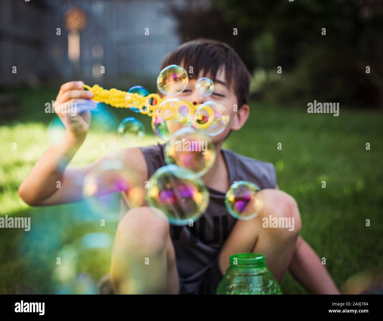 A young boy blowing bubbles outdoors on a summer day. Stock Photo
