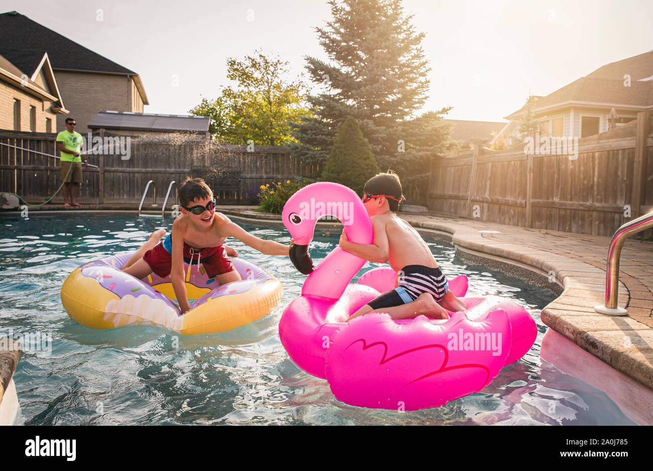 Two boys playing in a swimming pool on inflatable pool toys. Stock Photo