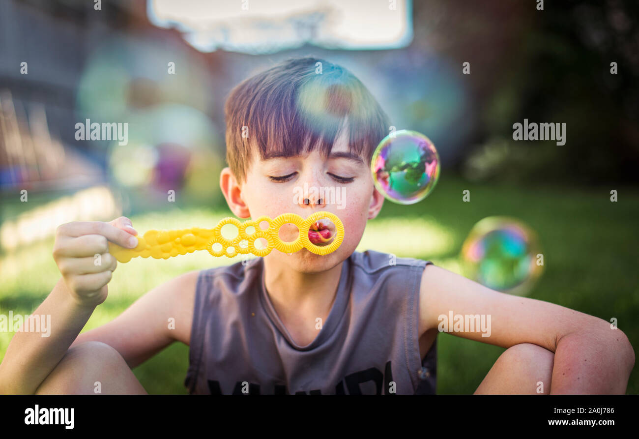 Young boy blowing bubbles outdoors on a summer day. Stock Photo