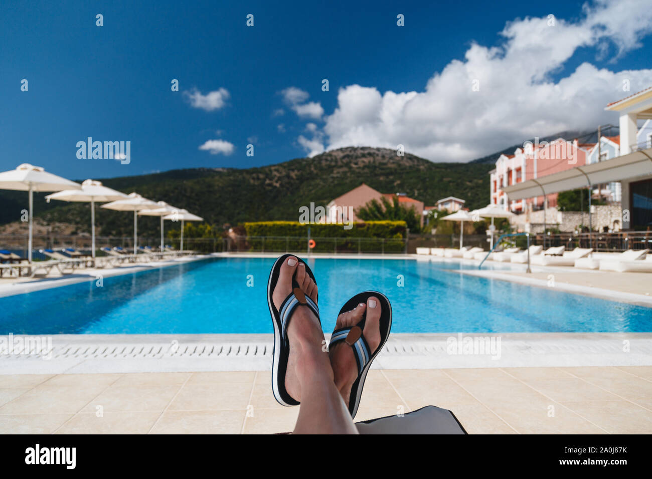 Close up view of young woman feet in blue flip-flops lying on a sun lounger with a swimming pool and blue sky at the background. Kefalonia island Stock Photo