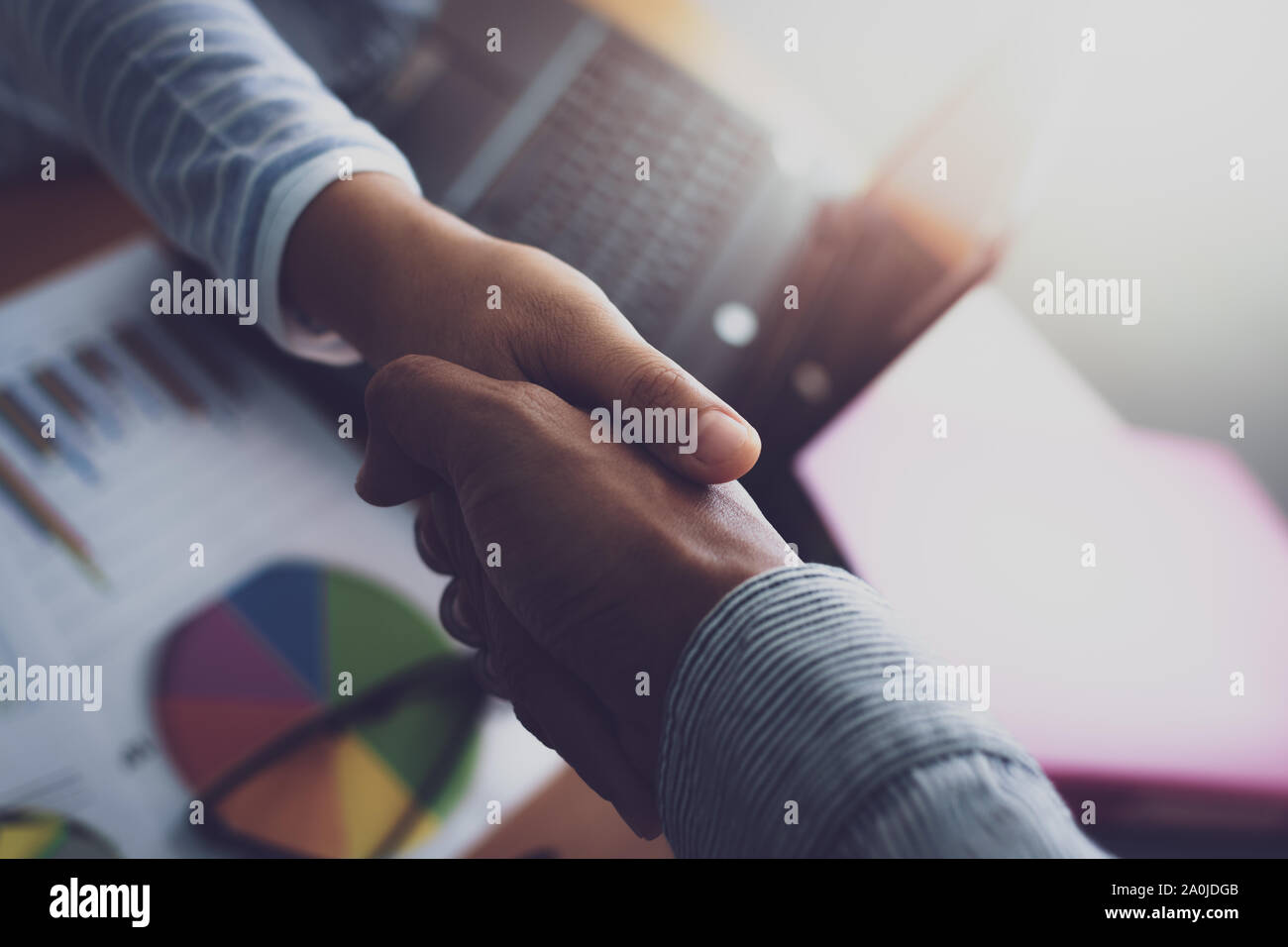 Two colleagues shaking hands together celebrating finished work. Business concept. Stock Photo