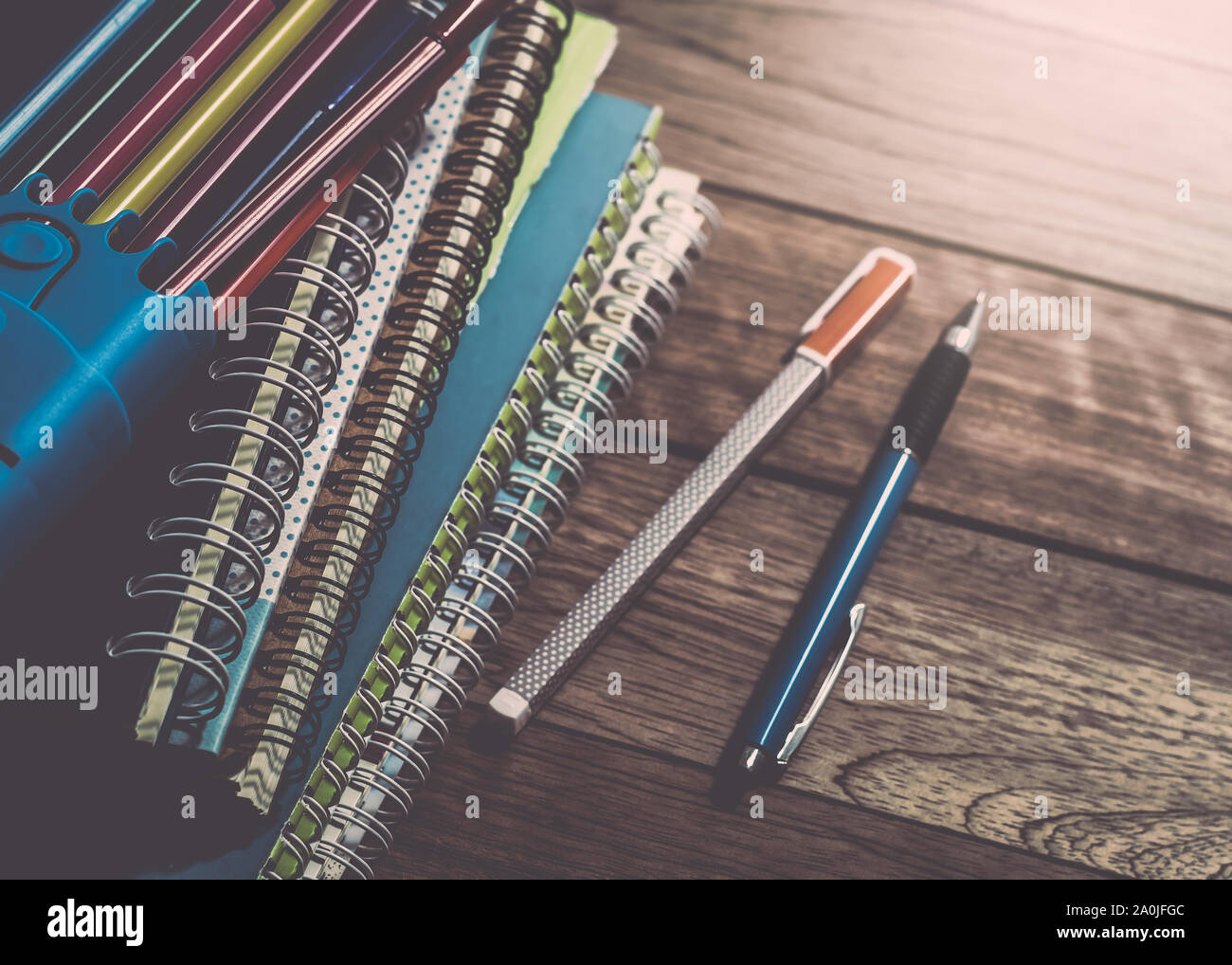 Heap of notebook with pens on wooden table under light in vintage style Stock Photo