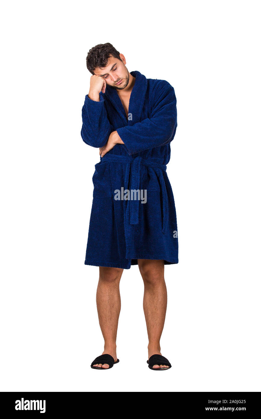 Full length portrait of sleepy young man wears blue bathrobe holding hand to forehead, eyes closed feel tired needs to sleep isolated on white backgro Stock Photo