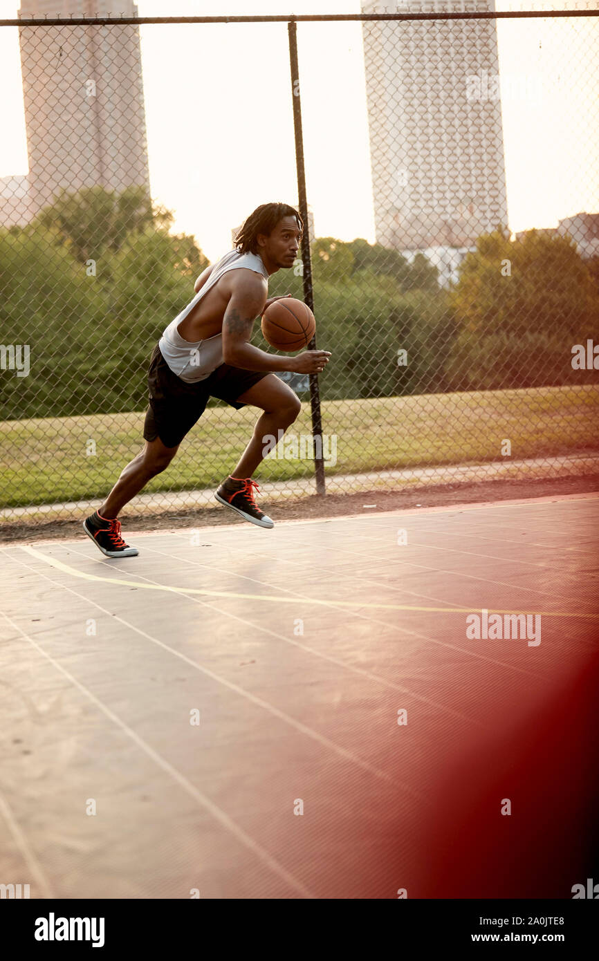 African-American man playing basketball outdoors Stock Photo