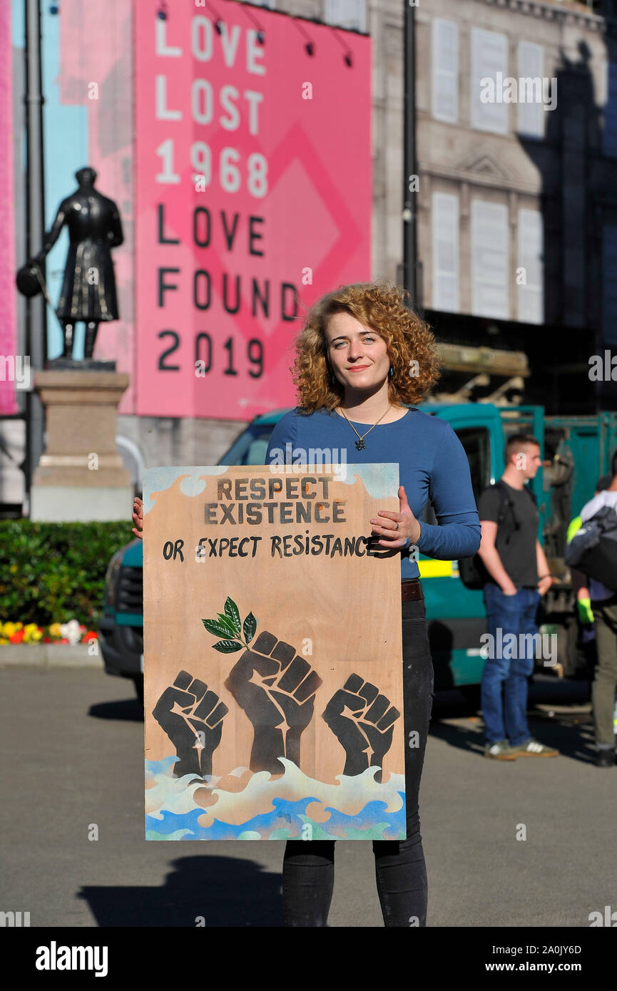 Glasgow, UK. 20 September 2019.  PICTURED: A climate change protestor stands beside a sign which reads 'RESPECT EXISTANCE OR EXPECT RESISTANCE'. Will there be anything left for our future generations? Scenes from a planned protest in George Square this afternoon after strikes started a year ago by 16-year-old Swedish schoolgirl named Greta Thunberg. Hundreds of chalk marked slogans littered the concrete of George Square with protestors from all ages and backgrounds. Credit: Colin Fisher/Alamy Live News Stock Photo