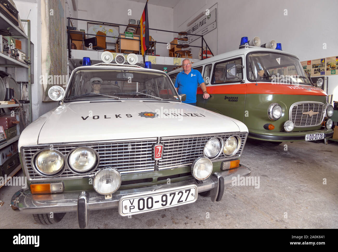 Trebus, Germany. 19th Sep, 2019. Günter Wehr, chairman of the IFA-Freunde Trebus, stands between a Lada (l) and a Barkas B1000 of the former Volkspolizei in a room full of objects from GDR times. The former German state on a small scale exists in the Brandenburg province. The IFA friends in Trebus will be offering an authentic journey through time into everyday life in the GDR on 14,000 square metres of space. Visitors indulge in memories during guided tours. Credit: Patrick Pleul/dpa-Zentralbild/ZB/dpa/Alamy Live News Stock Photo