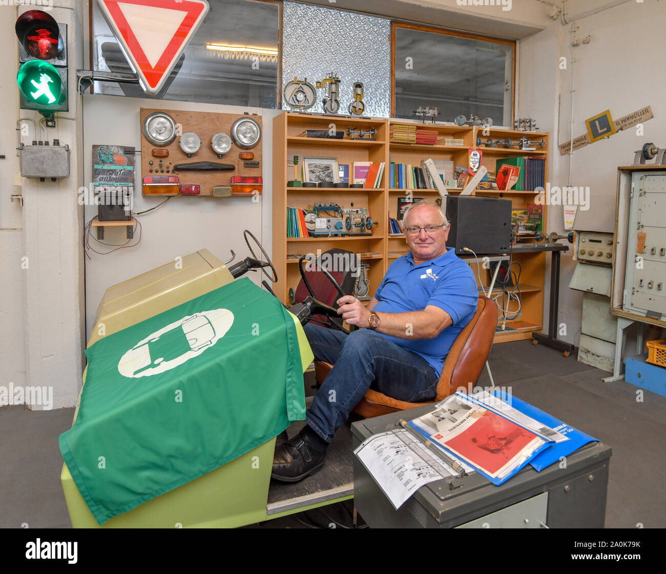 Trebus, Germany. 19th Sep, 2019. Günter Wehr, chairman of the IFA-Freunde Trebus, sits on a driving school simulator in a room full of objects from GDR times. The former German state on a small scale exists in the Brandenburg province. The IFA friends in Trebus will be offering an authentic journey through time into everyday life in the GDR on 14,000 square metres of space. Visitors indulge in memories during guided tours. Credit: Patrick Pleul/dpa-Zentralbild/ZB/dpa/Alamy Live News Stock Photo