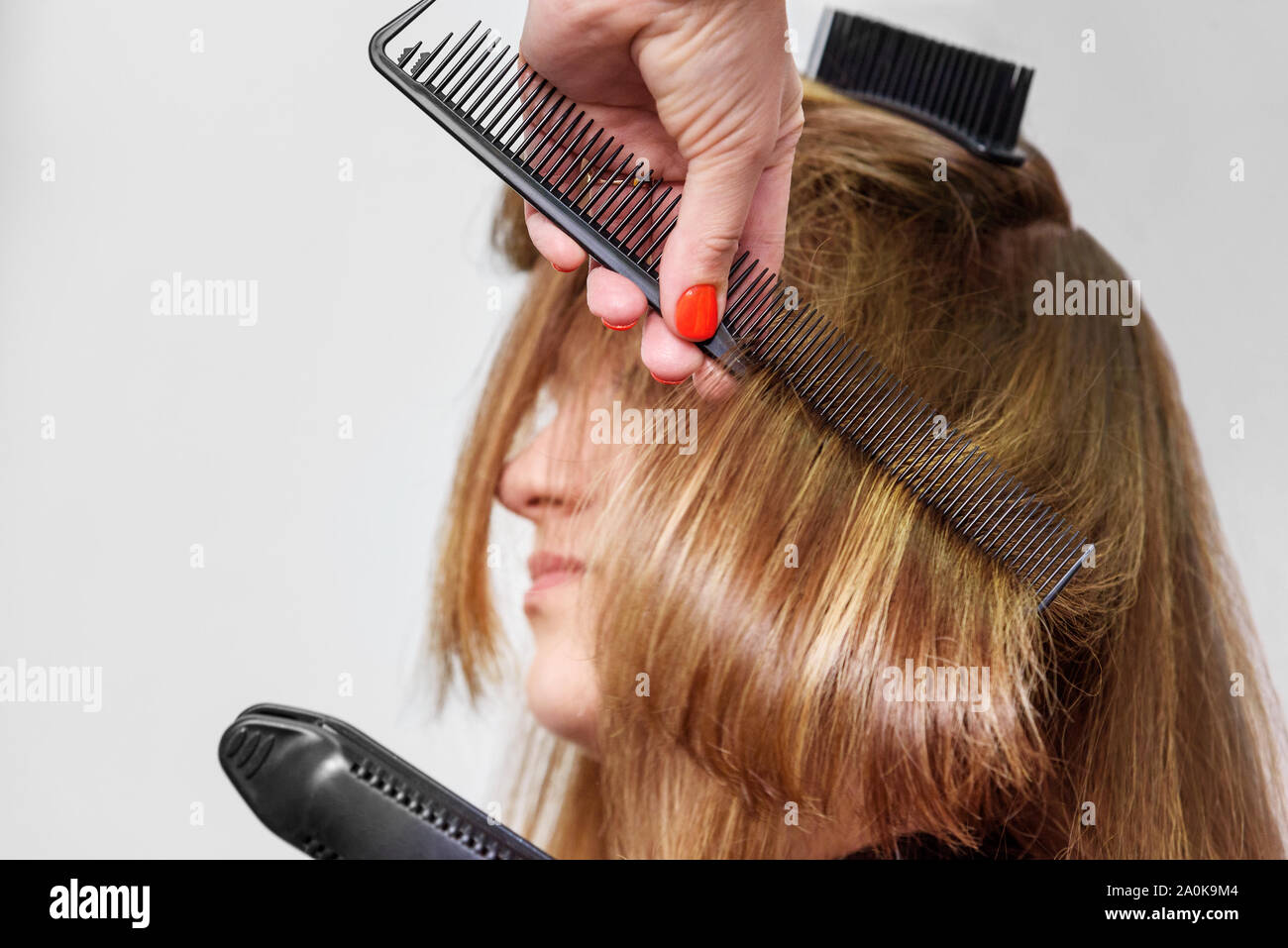 Professional hairdresser straightening long brown hair with hair irons in beauty salon. Close-up Stock Photo