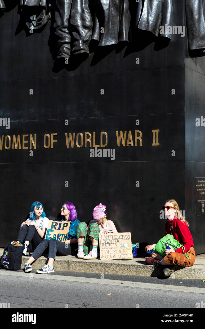 20 September 2019, London, UK - Young teenage girls sitting on ground by the Monument to the Women of World War II holding a RIP Earth sign at the Global Climate Strike in Westminster Stock Photo