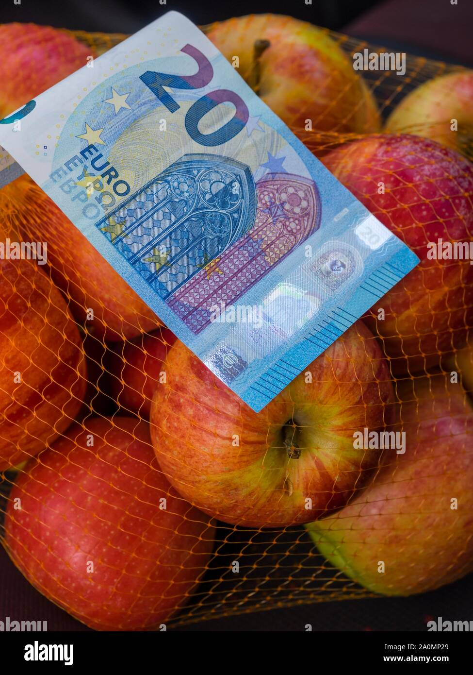 Apple fruit in backet and paper banknote money 20 twenty Euros Euro European Europe Stock Photo