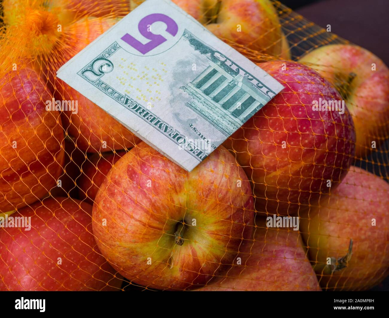 Apple fruit in backet and paper banknote money 5 five Dollars Dollar USA American Stock Photo