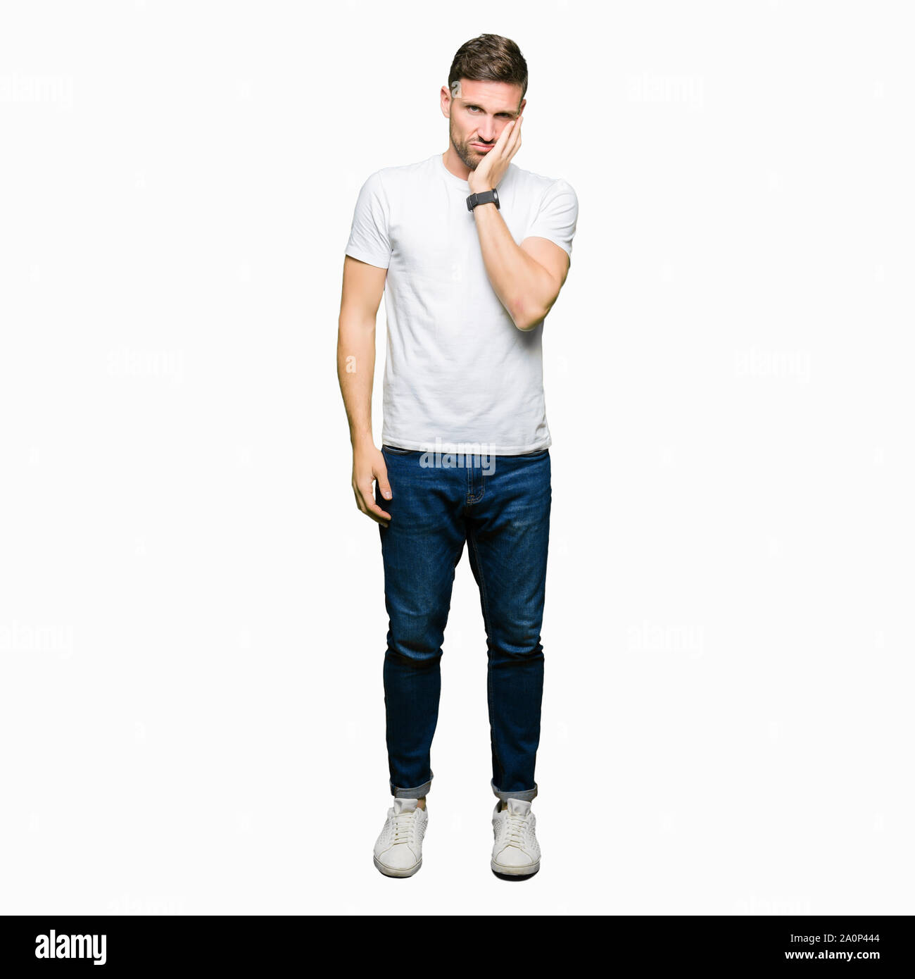 Handsome man wearing casual white t-shirt thinking looking tired and bored with depression problems with crossed arms. Stock Photo