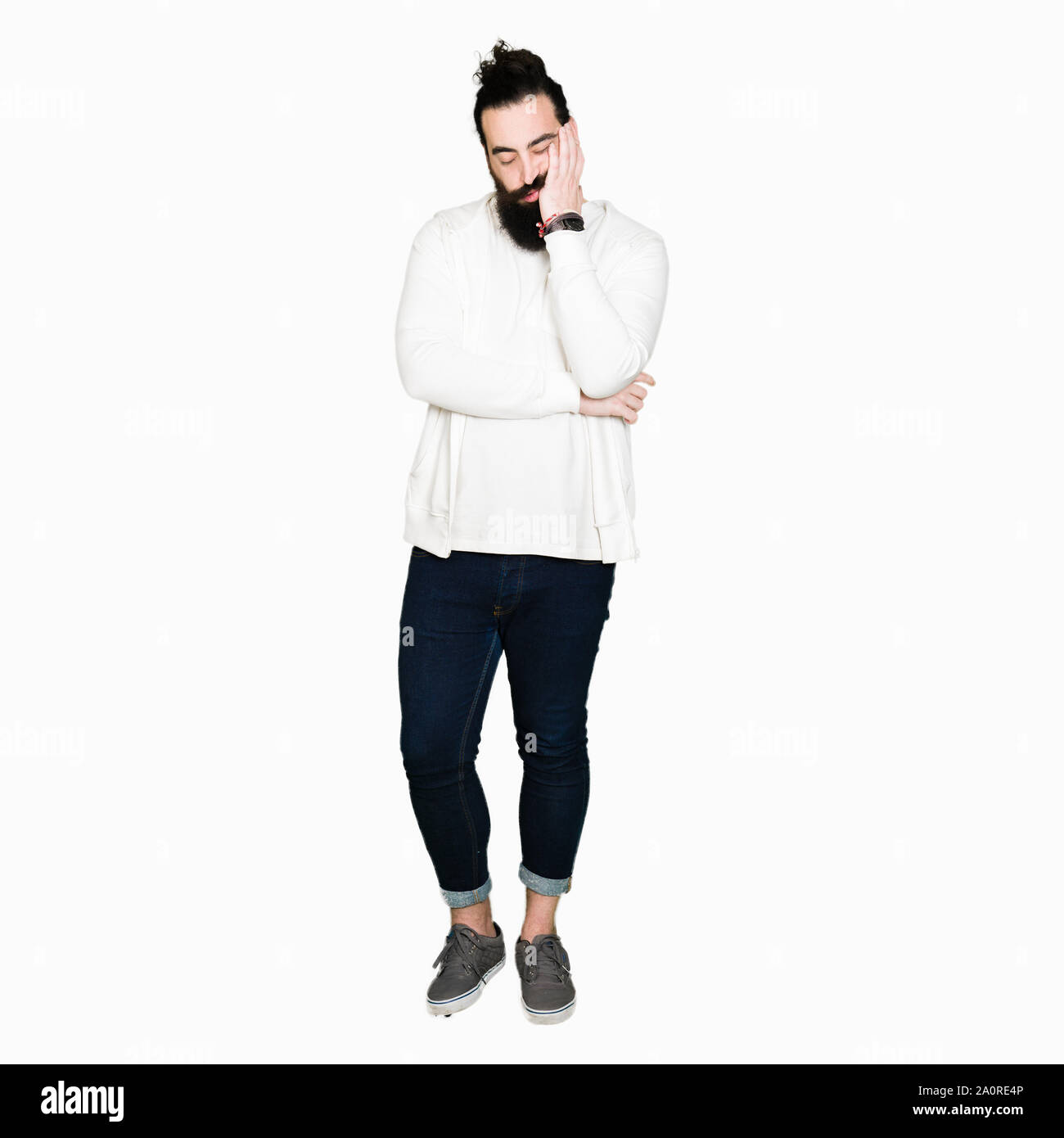 Young man with long hair and beard wearing sporty sweatshirt thinking looking tired and bored with depression problems with crossed arms. Stock Photo