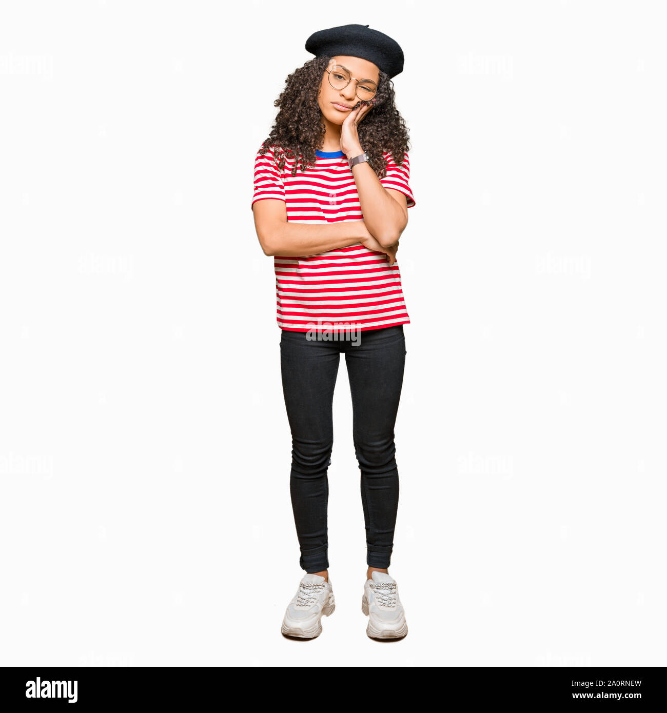 Young beautiful woman with curly hair wearing glasses and fashion beret thinking looking tired and bored with depression problems with crossed arms. Stock Photo