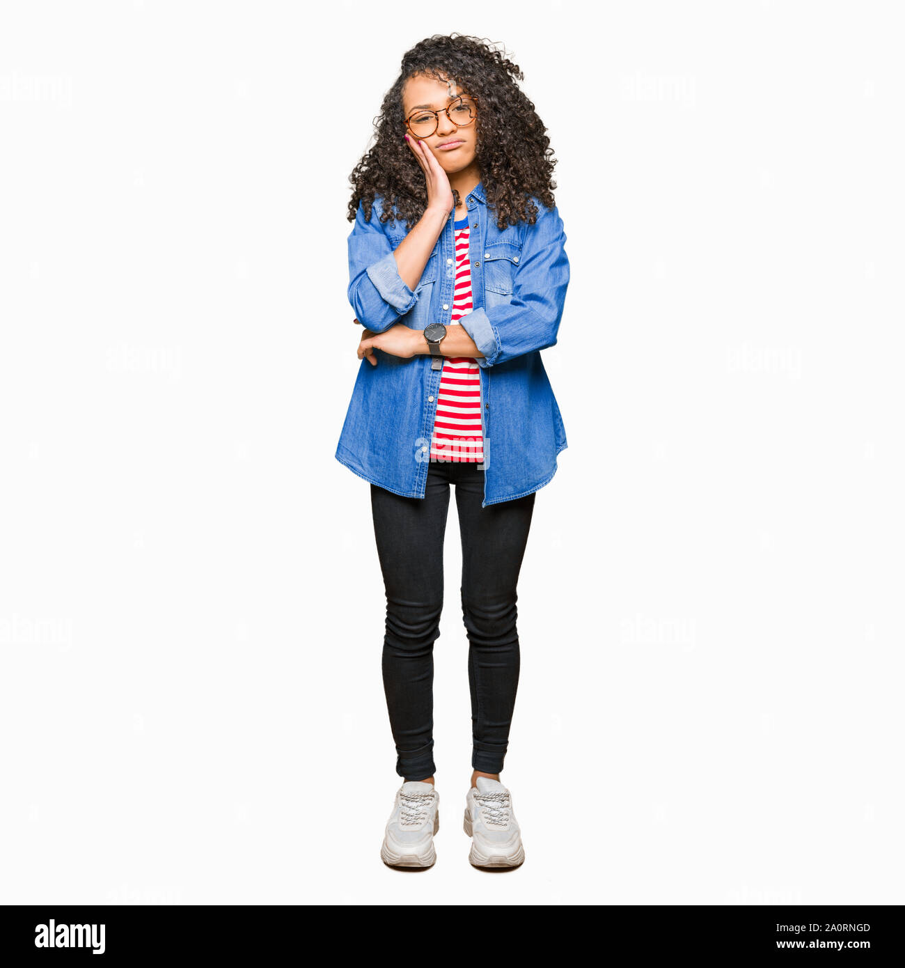 Young beautiful woman with curly hair wearing glasses thinking looking tired and bored with depression problems with crossed arms. Stock Photo