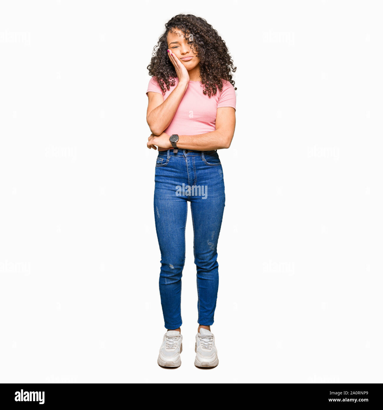 Young beautiful woman with curly hair wearing pink t-shirt thinking looking tired and bored with depression problems with crossed arms. Stock Photo