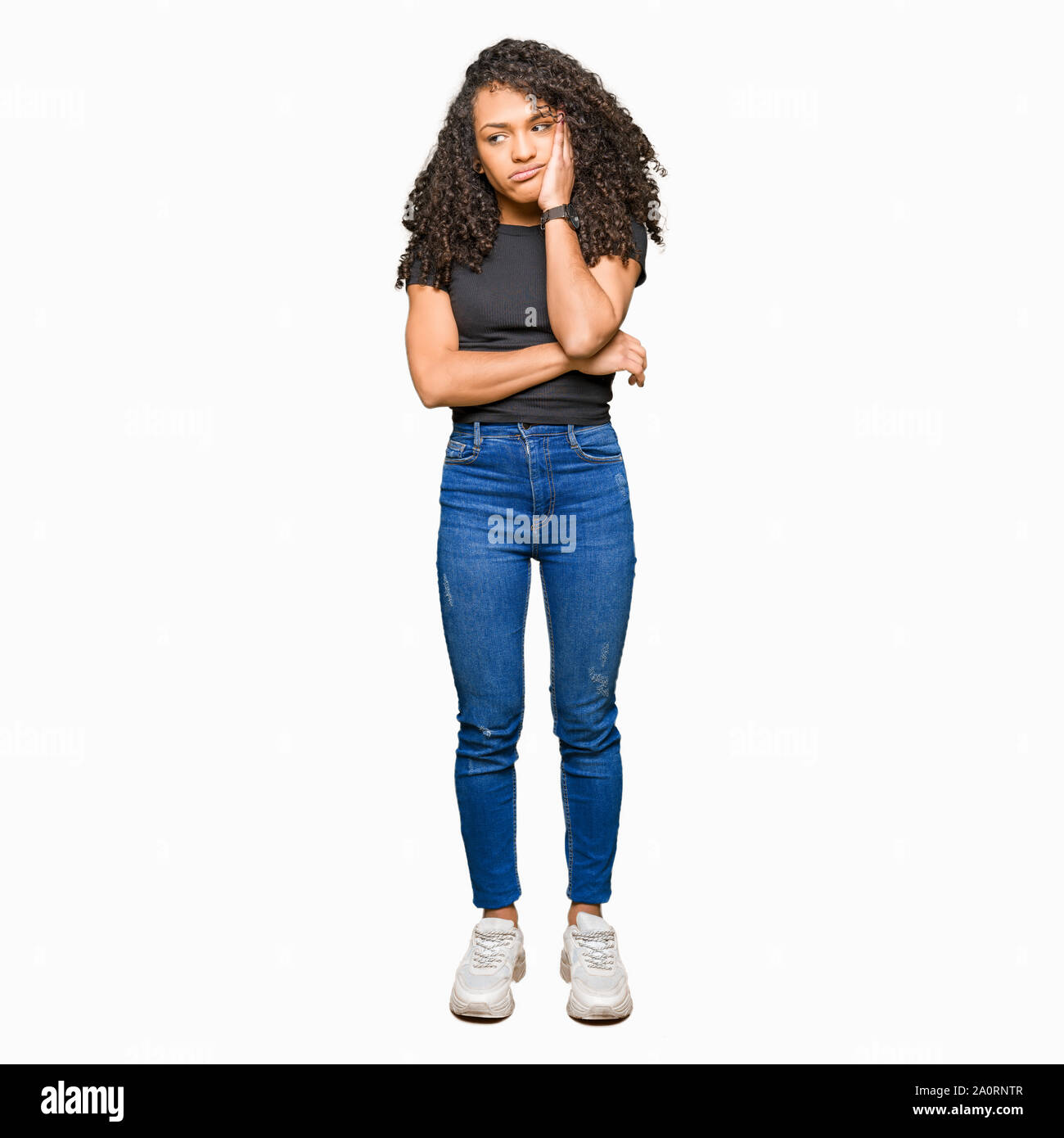 Young beautiful woman with curly hair thinking looking tired and bored with depression problems with crossed arms. Stock Photo